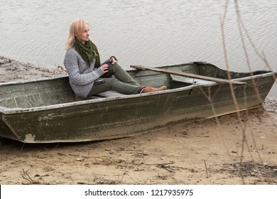 Beautiful blonde woman in old boat on river coast. Wearing worm wool sweater, khaki kargo jeans and green scarf. Maybe fisher lady or traveler