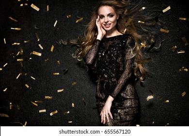 Beautiful blonde woman on black background with confetti