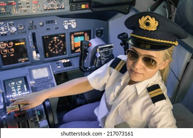 Beautiful blonde woman pilot wearing uniform and hat with golden wings - Modern aircraft cockpit ready for take off - Concept of female emancipation