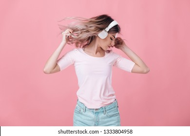 beautiful blonde woman in pink t-shirt and white headphones listens to music and dancing on pink background