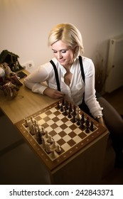 Beautiful blonde woman playing chess.Concept of rules,steps and decisions we take in life.Woman leaned,thinking about her next move.Business strategy concept.