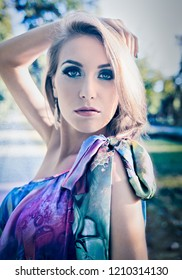 Beautiful blonde woman portrait with big blue eyes, sunkissed, wearing a silk colorful dress in the park, during daytime