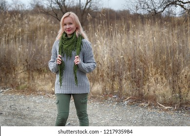 Beautiful blonde woman portrait on high grass nature landscape in autumn time. Wearing worm wool sweater, green scarf and khaki kargo jeans. Red lipstick makeup