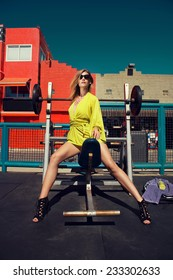 beautiful blonde woman posing in fashion clothes and jewelry at fitness center. Fashion photo with sunglasses