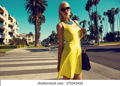 beautiful blonde woman posing with handbag in yellow dress and sunglasses walking across the street. Fashion photo