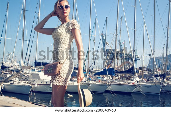 Beautiful blonde woman posing in harbor at sunny summer day. Girl wearing fashionable sunglasses, holding hat.