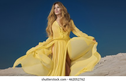 Beautiful blonde woman posing in maxi yellow dress on desert. Summer photo. Blue sky. Sunny day.