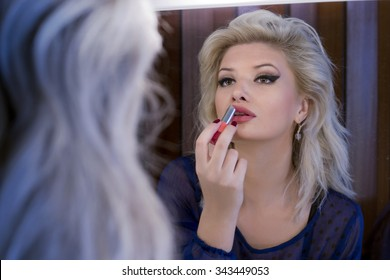 Beautiful blonde woman putting lipstick on