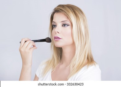 Beautiful blonde woman putting on makeup
