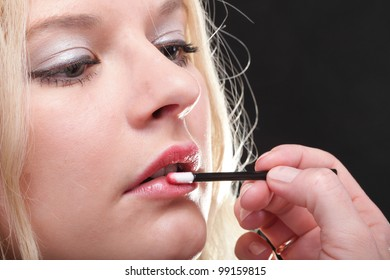 Beautiful blonde woman putting on makeup red lipstick