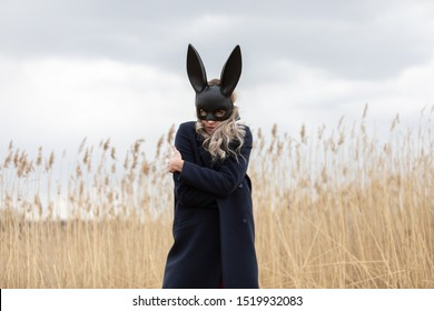 Beautiful blonde woman with scared face in black bunny mask posing outdoors. Monochrome image.