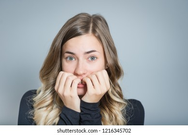 beautiful blonde woman scared isolated over black background