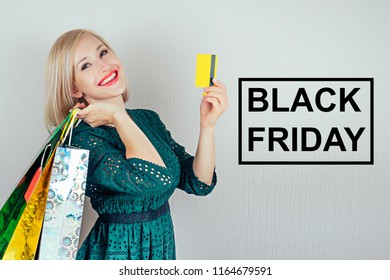 beautiful blonde woman shopaholic in a green dress with shopping bags and plastic credit card . concept of shopaholism and sales