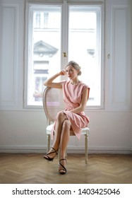 Beautiful blonde woman sitting on a chair in front of a white window.
