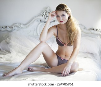 Beautiful blonde woman sitting on a bed and looking