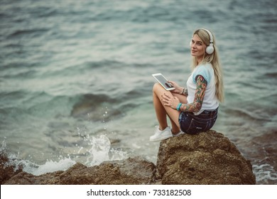 Beautiful blonde woman sitting on a rock by the sea and listening to music on stylish headphones on the tablet. hands with a tattoo. The style of summer holiday. Modern girl