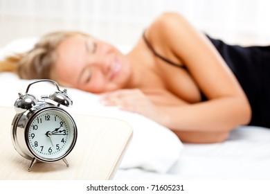 beautiful blonde woman sleeping on white bed