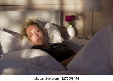 Beautiful blonde woman sleeps in bed, in wooden house.