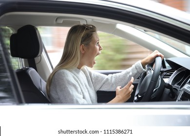 Beautiful blonde woman with a smartphone in her hand looking horrified while driving a car