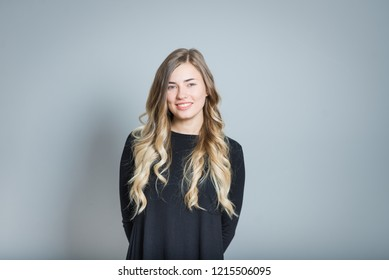 beautiful blonde woman smiling, isolated over gray background