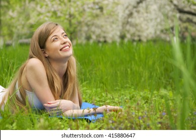 Beautiful blonde woman is smiling and looking at the sky