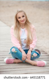 Beautiful blonde woman smiling and sitting on sand beach outdoor portrait. Happy young girl smile and resting at the sea coast. Cheerful romantic lady with long blond hair outdoors