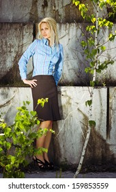 Beautiful blonde woman standing by a stone wall