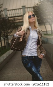 Beautiful blonde woman in sunglasses wearing loose dress in city. Brown color toning photo