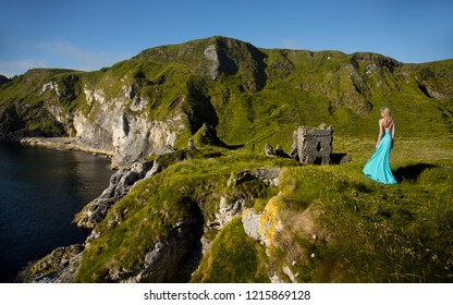 Beautiful blonde woman in turquoise green long dress, stands in the middle of a field, close to the sea, in Ireland.