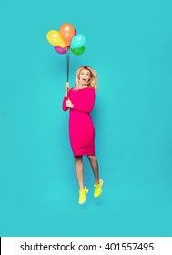 beautiful blonde woman very energetic, smiling and jumping with some colored balloons on blue background