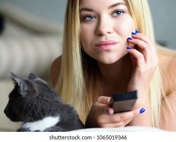 Beautiful blonde woman wake up early morning lie in bed with cat hold remote control device in arm watching tv. Having fun home morning show idling during weekend or day off concept