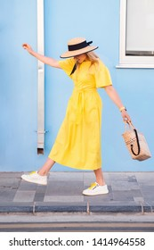 Beautiful blonde woman walking in yellow dress at Paphos old city with colorful door and house. Travel to Cyprus. Fashion summer photo