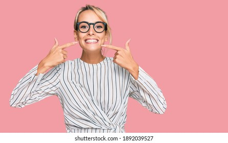 Beautiful blonde woman wearing business shirt and glasses smiling cheerful showing and pointing with fingers teeth and mouth. dental health concept.