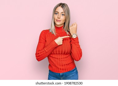 Beautiful blonde woman wearing casual clothes in hurry pointing to watch time, impatience, looking at the camera with relaxed expression