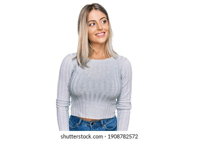 Beautiful blonde woman wearing casual clothes looking away to side with smile on face, natural expression. laughing confident.