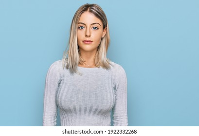 Beautiful blonde woman wearing casual clothes relaxed with serious expression on face. simple and natural looking at the camera.