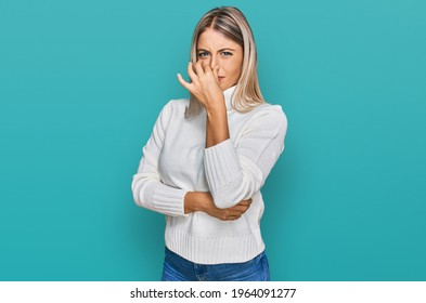 Beautiful blonde woman wearing casual turtleneck sweater smelling something stinky and disgusting, intolerable smell, holding breath with fingers on nose. bad smell