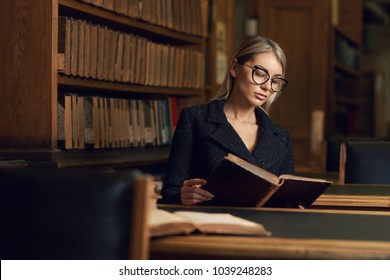 Beautiful blonde woman wearing elegant black tweed jacket and glasses sitting at desk beside bookshelf and reading book. Young gorgeous female student studying at library. Smart is new sexy concept.