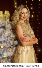 Beautiful blonde woman is wearing fashion golden dress over xmas tree