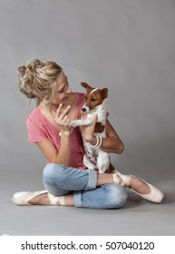 Beautiful blonde woman wearing jeans and ballet shoes playing with cute Jack Russel Terrier dog.