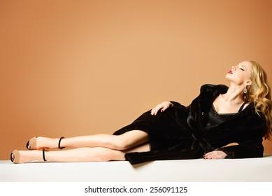 Beautiful blonde woman wearing mink fur coat. Fashion, beauty. Luxurious lifestyle. Studio shot.