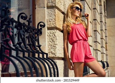 Beautiful blonde woman wearing pink jumpsuit and black sunglasses posing on the wall. Fashion photo with accessories..