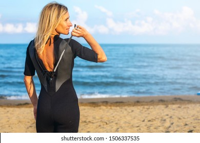 Beautiful blonde woman wears surf wetsuit