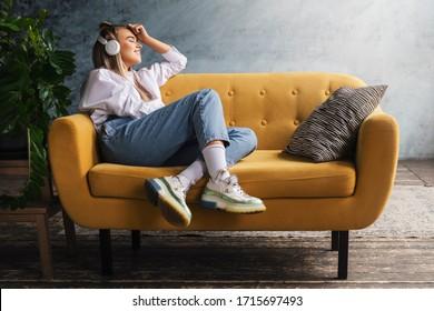 白いヘッドフォンを持つ美しい金髪の女性が黄色いソファに座り、音楽やポッドキャストを楽しみます。
