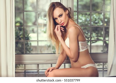 Beautiful blonde woman in white lingerie posing near a window. Young girl wearing underwear with long hair looking at camera.