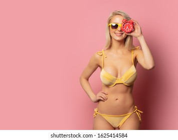 Beautiful blonde woman in yellow bikini and sunglasses with alarm clock on pink background