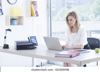 Beautiful blonde young business woman in office working on her laptop