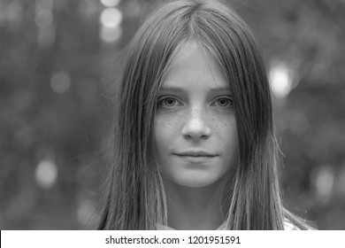 Beautiful blonde young girl with freckles outdoors on nature background in autumn, close up portrait, black and white