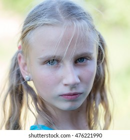 Beautiful blonde young girl in nature, portrait close up