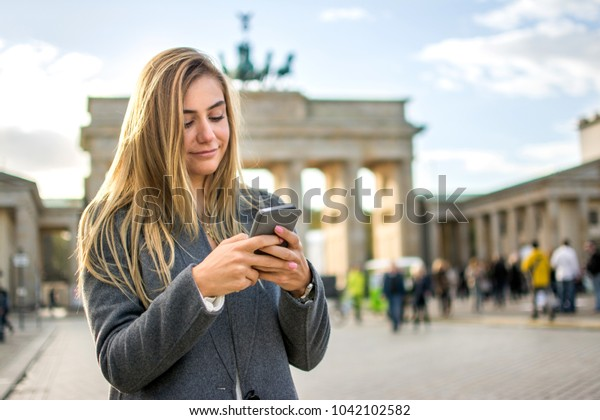 Beautiful blonde young girl using phone in front of Brandenburg Gate in Berlin, Germany,